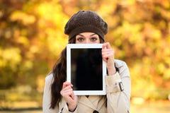 显示片剂屏幕的妇女在秋天 库存照片