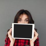 显示片剂屏幕的年轻深色的妇女 图库摄影