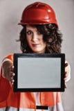 显示片剂的安全帽的性感的女孩 免版税库存图片