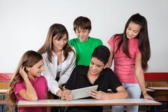 显示片剂的少年男小学生对同学在 免版税图库摄影