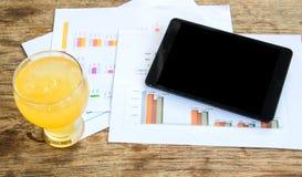 黑显示片剂,冷玻璃杯柠檬水,图表数据analysi 免版税库存图片