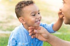 显示牙的可爱的孩子对他的父亲 免版税图库摄影