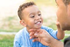 显示牙的可爱的孩子对他的父亲 库存图片