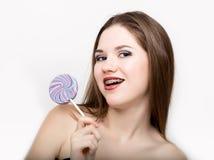 显示牙齿括号和拿着糖果的青少年的女孩画象 免版税库存图片