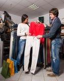 显示牛仔裤和衬衣的售货员对美丽的妇女 免版税库存图片