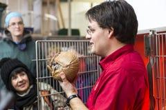 显示犰狳的红色衬衣的动物园技术员在球对小组妇女 库存照片