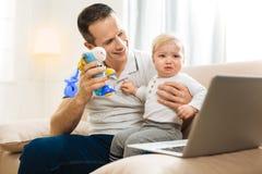 显示玩具的亲切的殷勤父亲对他哭泣的婴孩和微笑 库存照片