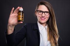 显示瓶维生素的成功的女性经理 图库摄影