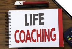 显示生活教练的手写的文本 企业在笔记薄便条纸写的个人教练帮助的概念文字,木bac 免版税库存图片