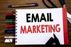 显示电子邮件行销的手写的文本 在笔记本写的网上网促进的企业概念,木背景与  库存图片