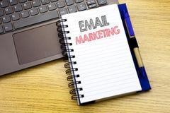 显示电子邮件行销的文字文本 在木背景的笔记本书写的网上网促进的企业概念 免版税库存照片