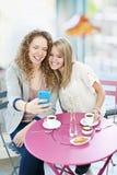 显示电话的妇女对朋友 免版税库存图片