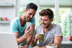 显示电话的微笑的人对朋友 免版税库存照片