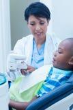 显示男孩假肢牙的牙医 免版税库存图片