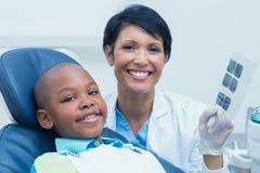 显示男孩他的嘴X-射线的女性牙医 免版税库存照片