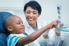 显示男孩他的嘴X-射线的女性牙医 免版税图库摄影