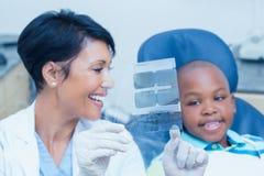 显示男孩他的嘴X-射线的女性牙医 免版税库存图片