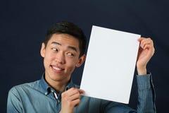 显示白色拷贝空间页的滑稽的年轻亚裔人 免版税库存照片
