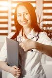 显示白色的制服好或认同标志的年轻愉快的快乐的医生与赞许 库存图片