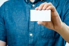 显示白色空白的名片的人被隔绝 在卡片的焦点 免版税库存照片