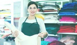 显示白色织品的卖主 免版税库存照片