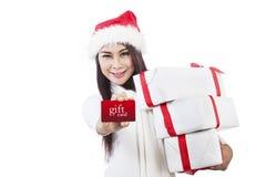 显示礼品看板卡和圣诞节礼物的亚裔妇女 库存图片