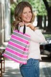 显示礼物袋子的美丽的妇女 免版税库存图片