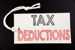 显示税收减免的手写的文本说明 企业在pric写的财务接踵而来的税钱扣除的概念文字 库存照片