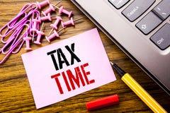 显示税时间的手写的文本 征税在木的桃红色稠粘的便条纸写的财务提示的企业概念 库存照片