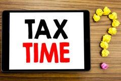 显示税时间的文字文本 征税在木背景的片剂计算机写的财务提示的企业概念 库存照片