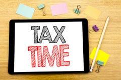 显示税时间的文字文本 征税在片剂膝上型计算机写的财务提示的企业概念,与sti的木背景 图库摄影