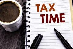 显示税时间的文字文本 征税在笔记本在木wo的笔访纸写的财务提示的企业概念 库存图片