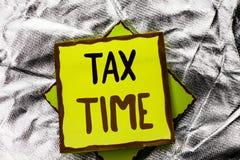 显示税时间的文本标志 在被堆积的St写的概念性照片征税最后期限财务薪水会计付款收入收支 免版税库存图片