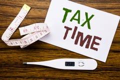 显示税时间的概念性手文字文本说明 征税在稠粘的便条纸写的财务提示的企业概念 图库摄影