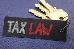 显示税法的手写的文本 企业征税在便条纸写的税收规则的概念文字附有钥匙, blac 图库摄影