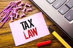 显示税法的手写的文本 征税在木backgro的桃红色稠粘的便条纸写的税收规则的企业概念 图库摄影