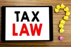 显示税法的文字文本 征税在木背景的片剂计算机写的税收规则的企业概念与qu 免版税库存照片