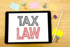 显示税法的文字文本 征税在片剂膝上型计算机写的税收规则的企业概念,与稠粘的木背景没有 免版税图库摄影