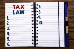 显示税法的文字文本 征税在笔记本便条纸写的税收规则的企业概念,与笔的木背景 库存照片