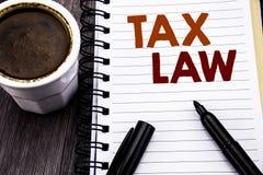 显示税法的文字文本 征税在笔记本在木木头后面的笔访纸写的税收规则的企业概念 免版税库存照片