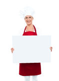 显示空白广告牌的愉快的女性主厨 库存图片
