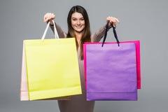 显示空白的五颜六色的购物袋和指向您灰色背景的微笑顾客佩带的礼服 免版税库存图片