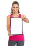 显示空白的剪贴板的愉快的健康少妇 免版税图库摄影