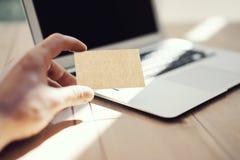 显示空白的工艺名片和使用现代膝上型计算机木头表的照片人 被弄脏的背景 大模型准备好为 免版税库存照片