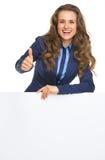 显示空白的广告牌和赞许的微笑的女商人 图库摄影