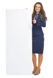 显示空白的广告牌和赞许的微笑的女商人 免版税库存图片