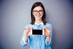 显示空白的智能手机屏幕的微笑的女实业家 免版税库存图片