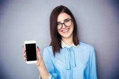 显示空白的智能手机屏幕的愉快的女实业家 库存图片