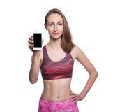 显示空白的智能手机屏幕的愉快的微笑的健身女孩在演播室 查出在空白背景 免版税图库摄影