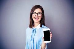 显示空白的智能手机屏幕的笑的女实业家 库存图片